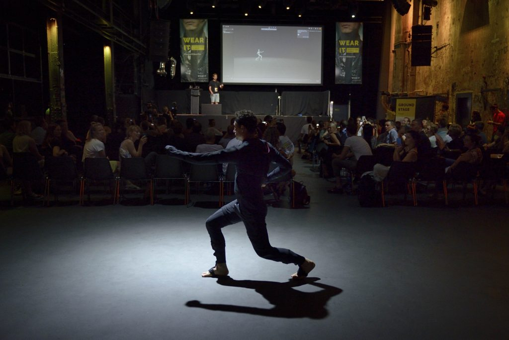 The image shows a demonstration of wearable technology presented at the Wear It Innovation Summit 2019.